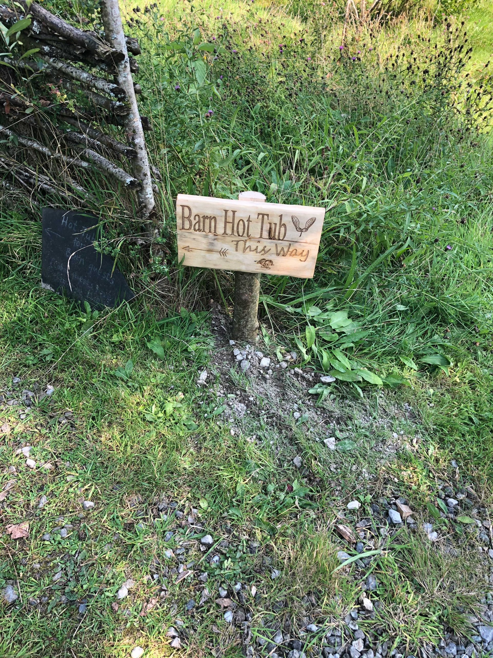 Rustic wooden sign in woods reads Barn Hot Tub This Way